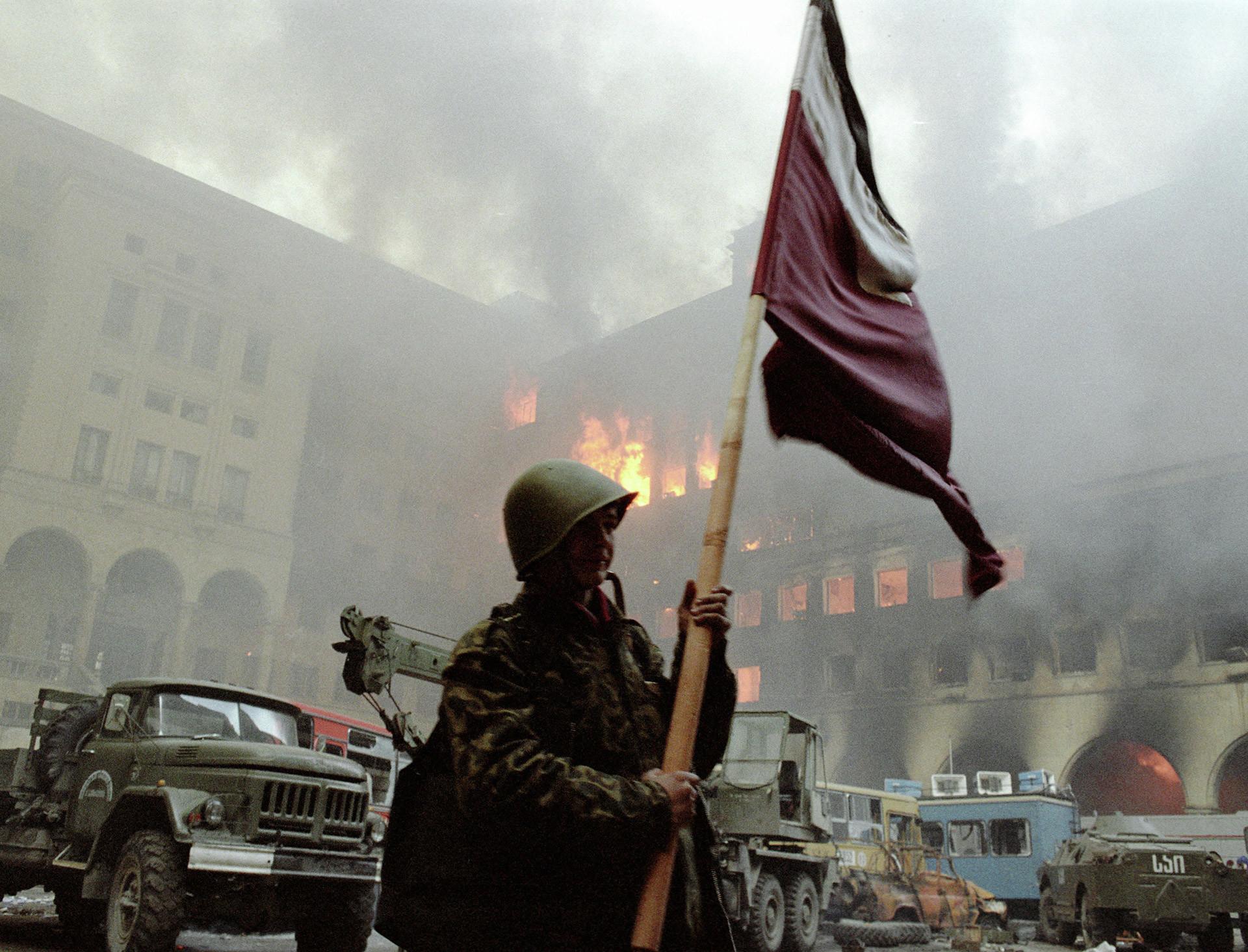Солдат держит знамя во дворе Дома правительства наутро после свержения режима Звиада Гамсахурдиа.